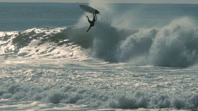 Surfer is trying to ride a big wave but he fails. Extreme sports and power of crushing waves.