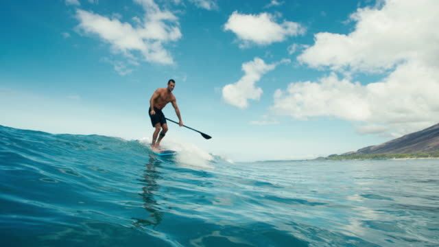 Surfer on blue ocean wave stand up paddleboarding video