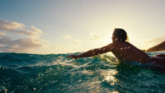 Surfer paddling over blue ocean wave at sunset in slow motion