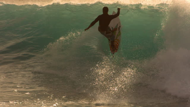 Surfer rides wave in late afternoon light, slow motion video