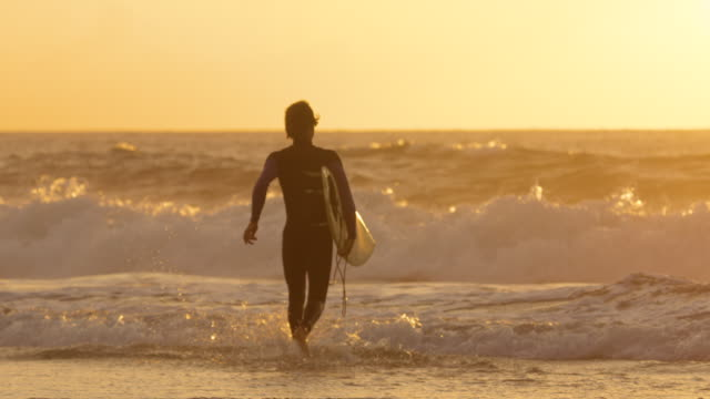 SLOW MOTION: Surfer running into water to surf breaking waves at golden sunrise.