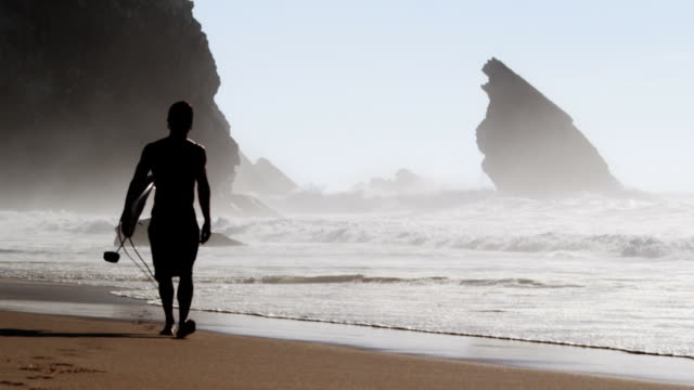 Surfer walking at the beach video