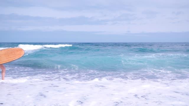 surfer with surfboard goes along the coastline along the surf - spoiler filmów i materiałów b-roll