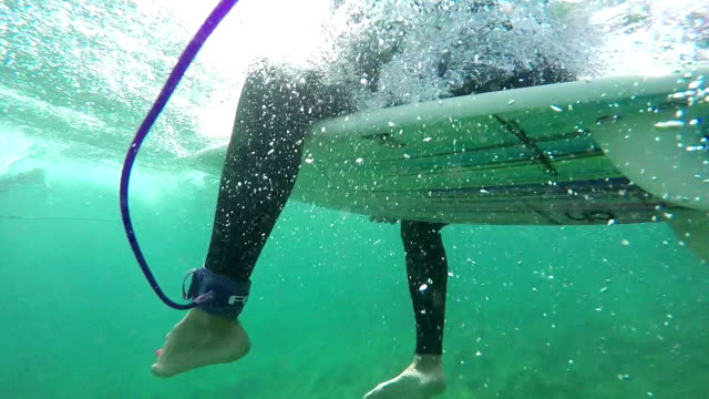 SLOW MOTION UNDERWATER: Surfer woman waiting for wave in line-up video