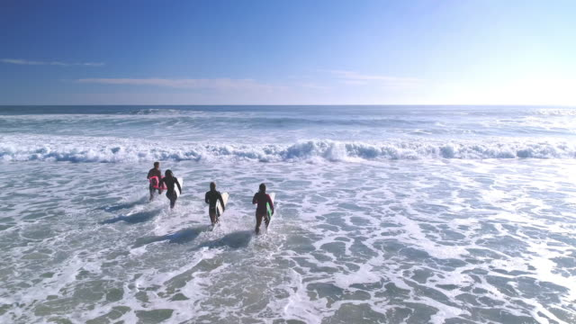 Surfers running into the sea Four surfers holding their surfboards and running into the sea. Sea, waves and blue sky in back. surf stock videos & royalty-free footage