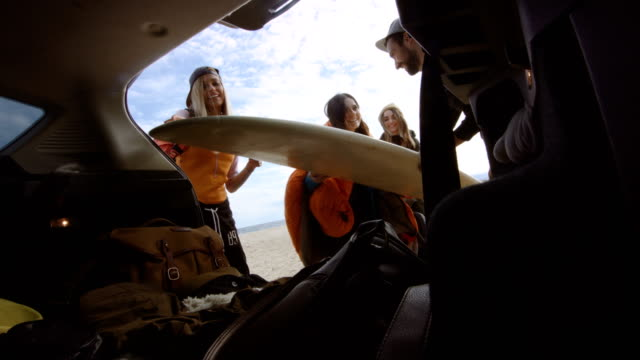 Surfers unpacking car trunk 4K video