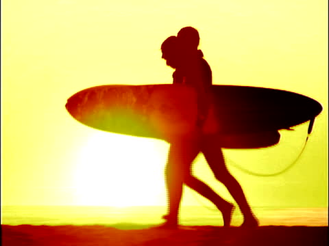 Surfers Walking on Beach #2 NTSC and PAL:  Two silhouetted surfers stroll along the beach as the sun sets behind them.   jetty stock videos & royalty-free footage