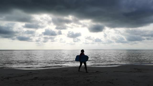 surfen-mädchen auf dem sandigen strand sonnenuntergang genießen. - ostsee stock-videos und b-roll-filmmaterial