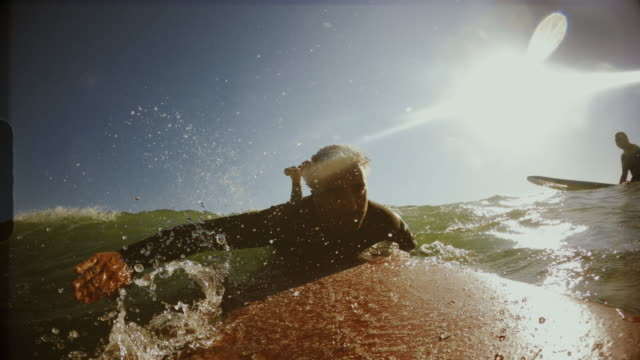 Surfing point of view pov with action camera: man on the longboard in Mediterranean Sea