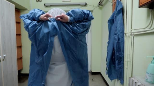 ameliyat bittikten sonra cerrah. - cerrahi önlük stok videoları ve detay görüntü çekimi