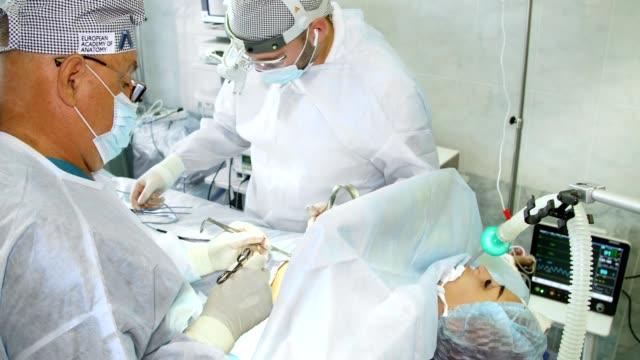 stockvideo's en b-roll-footage met chirurg en zijn assistent schone site voor borstimplantaat, het uitvoeren van cosmetische chirurgie in het ziekenhuis operatiekamer. borstvergroting plastische chirurgie. mammaplastie. borstkanker - breast cancer