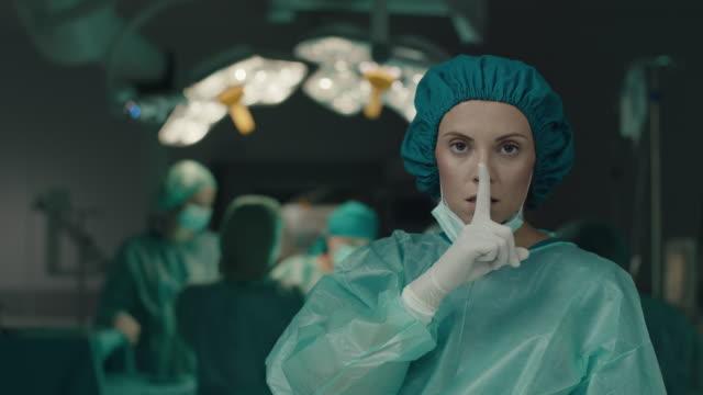 surgeon asking to be quiet with finger on lips - cisza filmów i materiałów b-roll