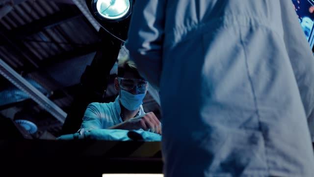 vídeos y material grabado en eventos de stock de el cirujano se concentra en la operación. el científico sostiene los instrumentos quirúrgicos, el equipo trabaja. unidad operativa. - autopsia