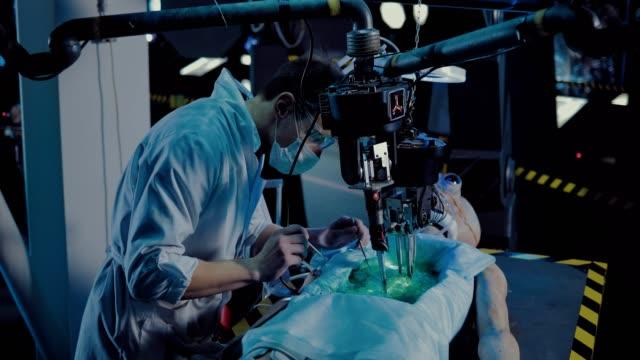 vídeos y material grabado en eventos de stock de el cirujano lleva a cabo la autopsia del alienígena. el doctor hace la operación con la ayuda de instrumentos y dispositivos. - autopsia