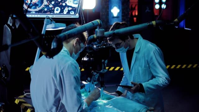 vídeos y material grabado en eventos de stock de el cirujano hace una autopsia de un alienígena, usted puede ver las entrañas. el técnico supervisa el trabajo y registra los datos. - autopsia