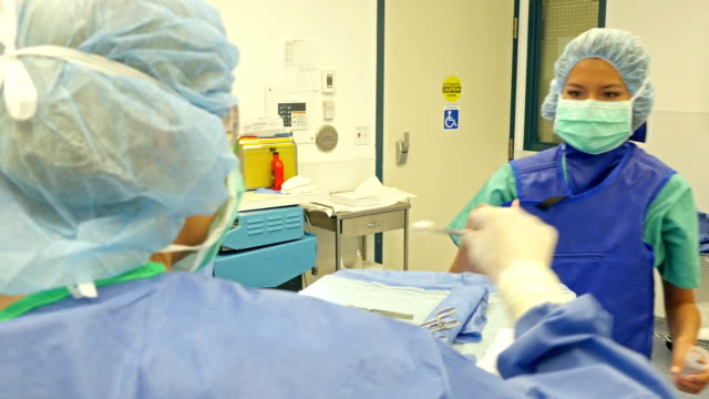 Surgeon is giving medical specimen to nurse video