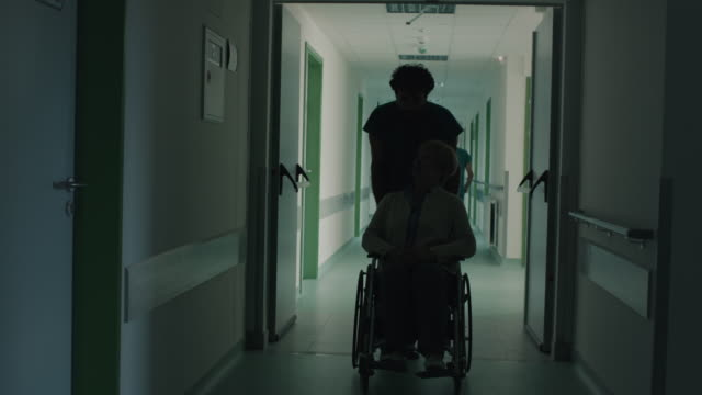 Surgeon pushing senior woman in wheelchair Surgeon pushing senior woman in wheelchair through hospital corridor pushing wheelchair stock videos & royalty-free footage