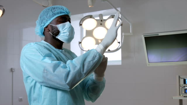 Surgeon puts on gloves in surgery video