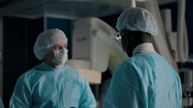 vídeos de stock e filmes b-roll de surgeon talking to colleagues in operating theater - exame médico procedimento médico
