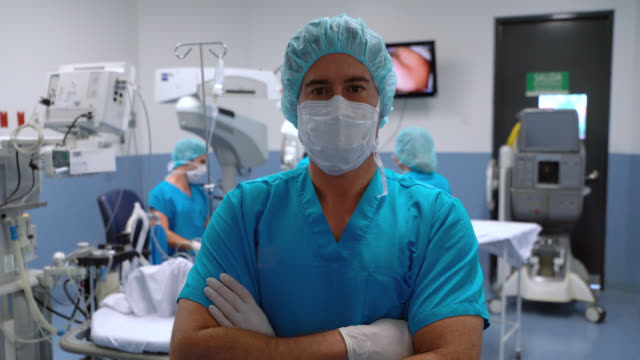 Surgeon wearing protective gear at an operating room facing camera crossing arms while team prepares patient Surgeon wearing protective gear at an operating room facing camera crossing arms while team prepares patient at background face mask videos stock videos & royalty-free footage