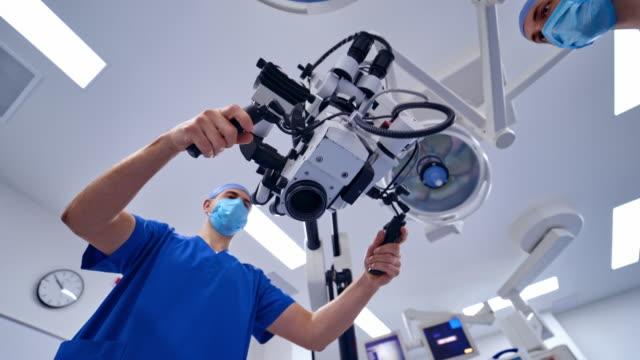 vídeos de stock, filmes e b-roll de cirurgião com microscópio intraoperatório. - equipamento médico