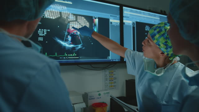 Video Surgeons discussing over monitor in operating room
