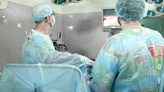 Surgeons follow the laparoscopic surgery, looking at screen video