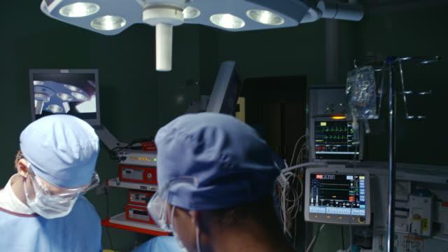 cerrahlar hasta üzerinde faaliyet scrubs - gazlı bez stok videoları ve detay görüntü çekimi