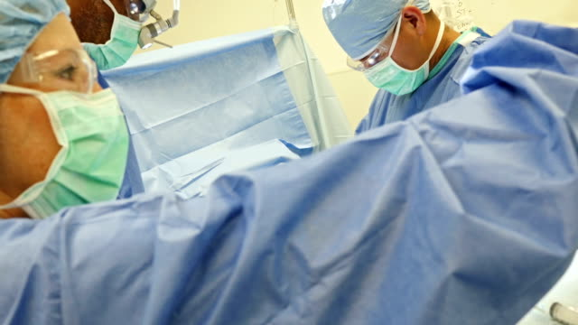 Surgeons operating on patient's abdomen video