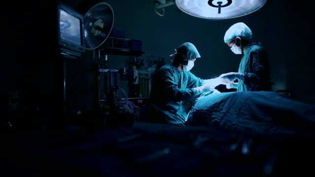 Surgery team operating in a surgical room Surgery team operating in a surgical room operating stock videos & royalty-free footage