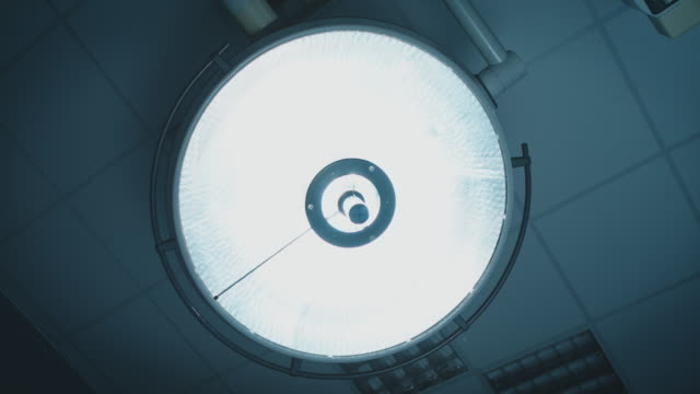 Surgical light in operating room Directly below shot of surgical light turning on. Handheld shot of electric light turning off. It is in operating room. surgical equipment stock videos & royalty-free footage