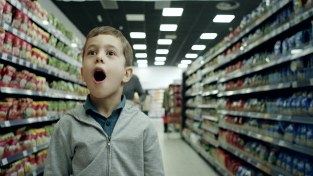 surprised boy in supermarket - sorpresa video stock e b–roll