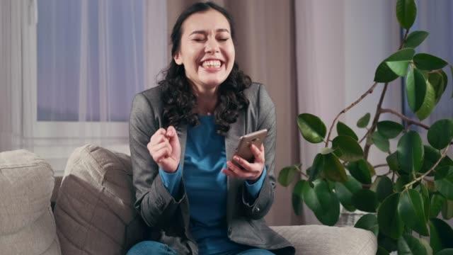 自宅で携帯電話を使って驚いたビジネスウーマン - 応援点の映像素材/bロール