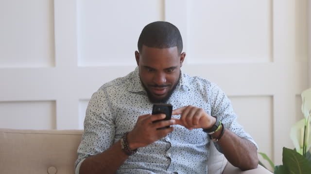 Surprised excited black man hold smartphone read good internet news