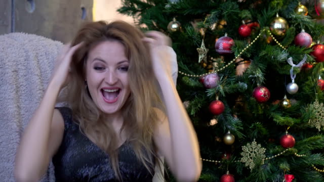 Surprised excited happy screaming woman on christmas tree background. video