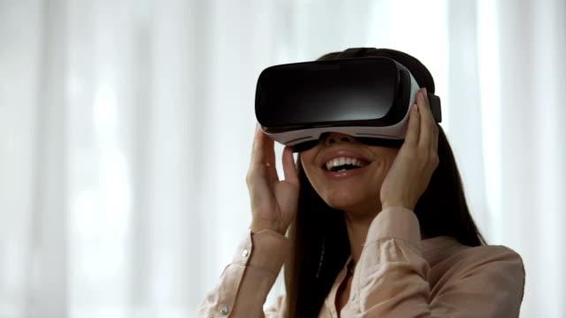 zaskoczona kobieta gra w grę wideo w wirtualnej rzeczywistości, obracając głowę w vr - rzeczywistość witrualna filmów i materiałów b-roll