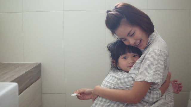 Surprised happy pregnant woman looking at pregnancy test in toilet