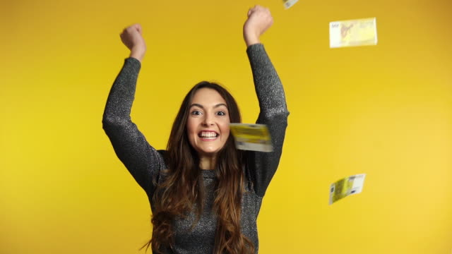 Surprised happy woman standing under money rain banknotes falling down Surprised happy woman standing under money rain banknotes falling down. Success, business, and fortune concept. Slow motion european union currency stock videos & royalty-free footage