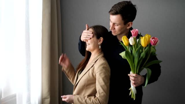 Surprised woman receive tulip flowers from her boyfriend