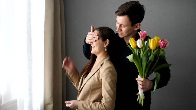 Surprised woman receive tulip flowers from her boyfriend girl stands and looks out the window at home. Behind the boyfriend comes, closes his eyes and gives a bouquet of tulips boyfriend stock videos & royalty-free footage