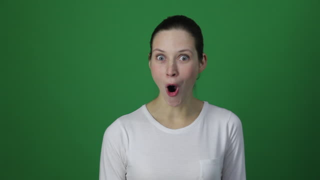 Surprised woman shouting, have big eyes and open mouth. Surprised woman shouting, have big eyes and open mouth. Studio shot, isolated in light green background background color stock videos & royalty-free footage