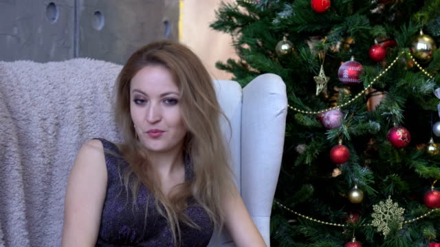 Surprised young woman shouting over christmas tree background. Looking at camera video