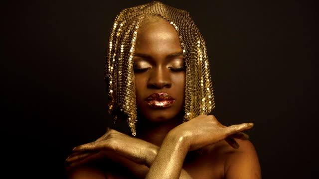 afrikalı-amerikalı kadın modeli altın parlak şapkalar ile gerçeküstü moda portre. yaratıcı vogue kavramı, siyah stüdyo arka plan - kep şapka stok videoları ve detay görüntü çekimi