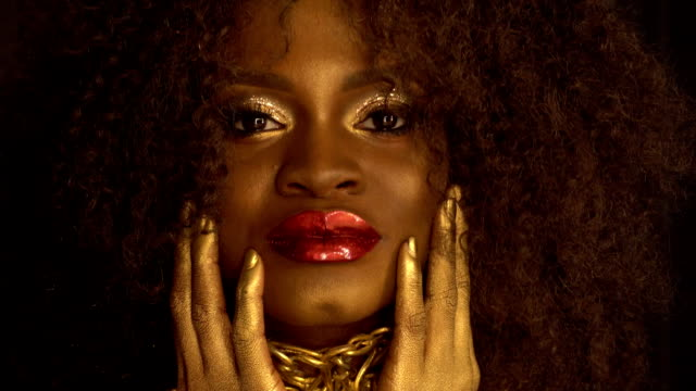 Surreal portrait of young african american female model with gold glossy makeup. Face art. Black studio background video
