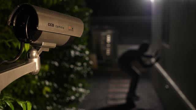 cctv övervakningskamera fånga scen av tjuv hoppa ner och försöka bryta sig in i ett hus på natten - vakta bildbanksvideor och videomaterial från bakom kulisserna