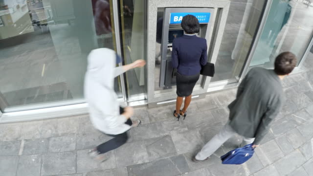 vídeos de stock e filmes b-roll de surveillance footage of an african-american woman being robbed at the atm in broad daylight and calling the police - roubar crime