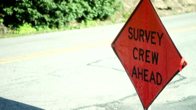 Survey Crew Ahead Orange sign on the road near construction zone