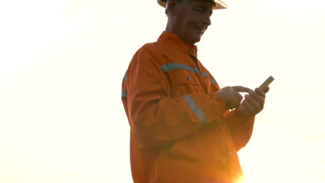 surveyor in orange jumpsuit and helmet types on smartphone - vídeo