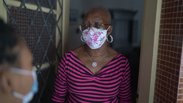Surveyor talking to senior woman in the doorway - wearing face maskSurveyor talking to senior woman in the doorway - wearing face mask video