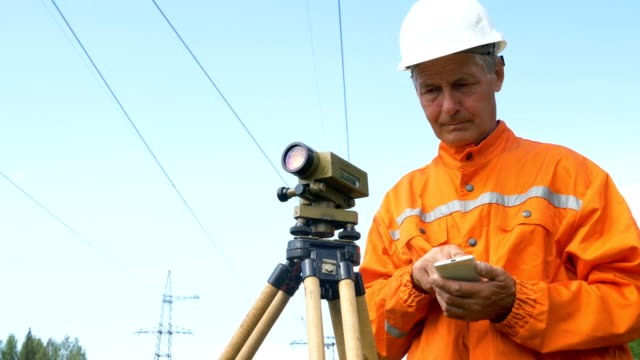 surveyor types on smartphone and looks through theodolite surveyor in orange jumpsuit and white helmet types on smartphone and looks through theodolite low angle shot survey stock videos & royalty-free footage